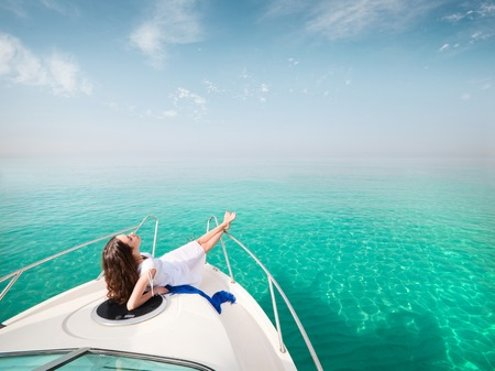 Photo pour Young sexy woman lies in white dress enjoying on yacht at the sea - image libre de droit