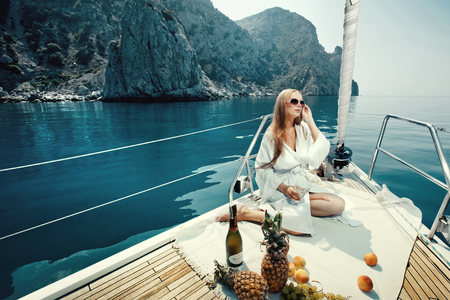 Foto de Luxury vacation at sea on yacht. Beautiful woman with wine, fruit and mobile phone on boat - Imagen libre de derechos