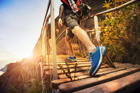 Photo for Men are hiking in the mountains, walking on a wooden bridge at sunset. Healthy lifestyle. - Royalty Free Image