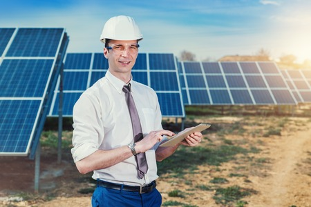 Photo pour Engineer at solar power station with solar panel tablet checks. Practical lessons on renewable energy power plants. - image libre de droit