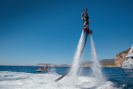 Photo pour Silhouette of a fly board rider at sea. Water summer extreme sports. - image libre de droit