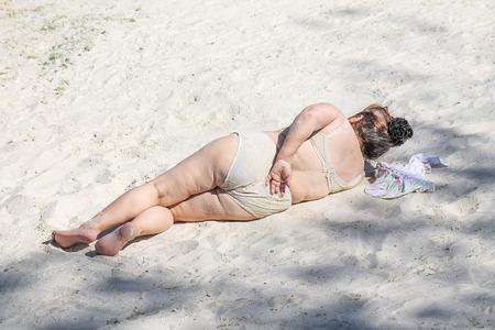 Foto de Old fat woman on the beach on white sand - Imagen libre de derechos