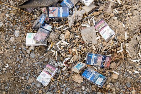 Photo for Various packs of cigarettes and cigarettes on earth are rubbish. Environmental disaster. - Royalty Free Image
