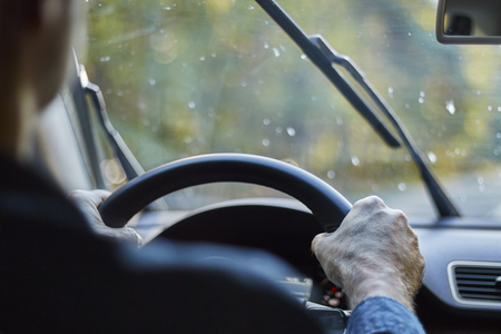 Photo for Back view of a man driving a car with moving windshield wipers during rain. - Royalty Free Image