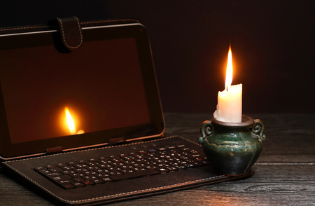 Photo for Blackout concept. Lighting candle near laptop with dark empty screen - Royalty Free Image