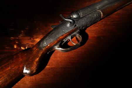 Foto de Ancient hunting shotgun closeup on wooden background - Imagen libre de derechos