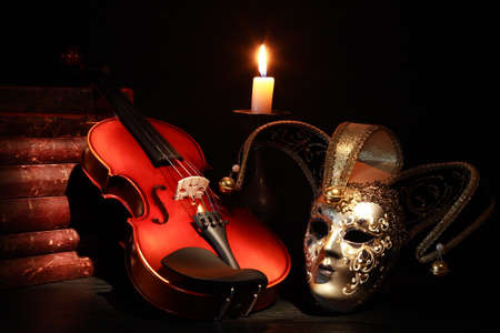 Photo for Nice violin near Venetian mask and candle against black background - Royalty Free Image