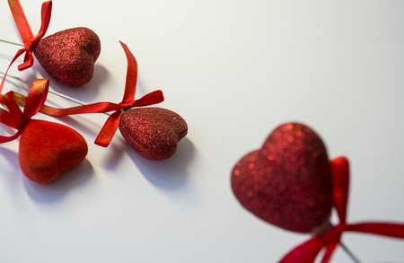 Photo for White background. Congratulation. Invitation. St. Valentine's Day. Red hearts in spangles and with bows. A decor for the house. Love. - Royalty Free Image
