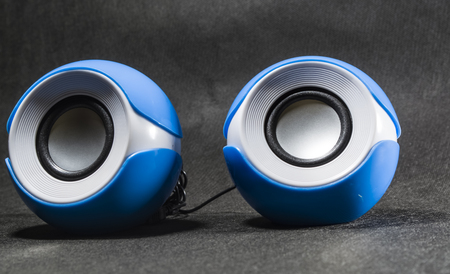 Photo for Portable small columns for music. Plastic. Black background. Blue and white colors. Round shape. Modern equipment. - Royalty Free Image