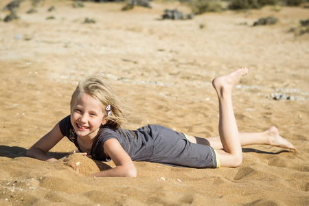 Photo for Little girl in gray dress is resting on the hot sand. The concept of fun in itema the summer holidays. - Royalty Free Image