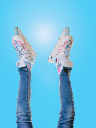 Foto für Baby's legs in jeans and roller skates on blue glare background. The concept of sports lifestyle. - Lizenzfreies Bild