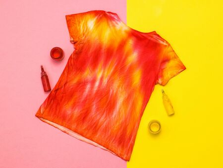 Photo pour T-shirt in the style of tie dye, paint and brush on a yellow and orange background. Staining fabric in tie dye style. Flat lay. - image libre de droit