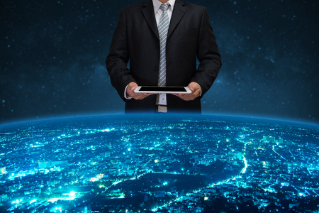Foto de businessman in black suite using tablet control the world - Imagen libre de derechos