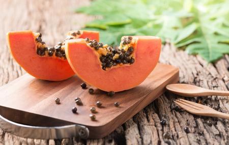 Photo for sliced papaya fresh fruit on wood block and old wood background - Royalty Free Image