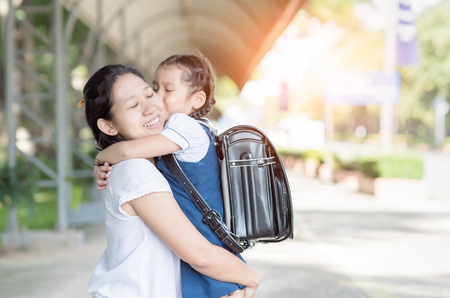 Foto de mother hug and kiss cute girl student before go to school, love and education concept. - Imagen libre de derechos