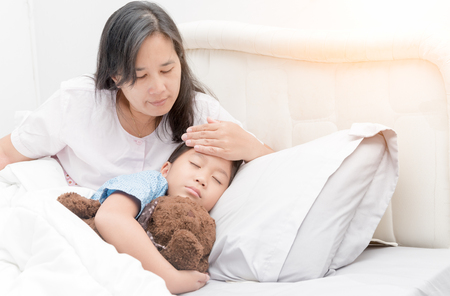 Photo pour Sick girl laying in bed and mother hand taking temperature. Sick child with fever and illness in bed, healthcare concept. - image libre de droit