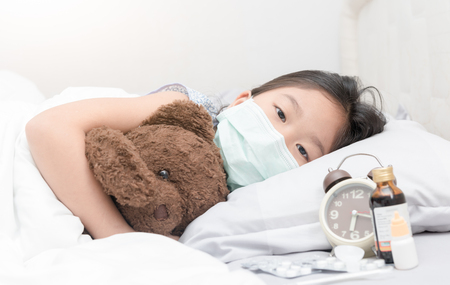 Photo pour Sick girl with hygienic mask laying on bed, healthy concept. - image libre de droit