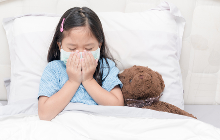 Foto de Asia little girl cough and waer hygienic mask.Virus protection and health care concept - Imagen libre de derechos