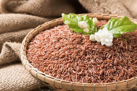 Foto de Jasmine brown rice beery  in bamboo basket on sack background, healthy food and diet concept.. - Imagen libre de derechos