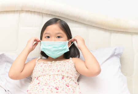 Foto de sick girl wear protection mask to protect against influenza virus in bed room, health care and sick child concept... - Imagen libre de derechos