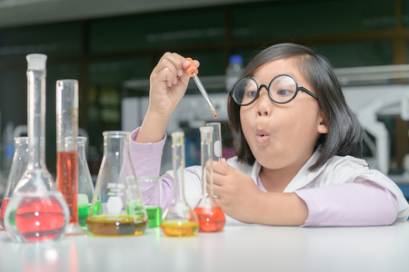 Foto de Excited little girl in lab coat making experiment with test tube in chemical laboratory, science and education concept.. - Imagen libre de derechos