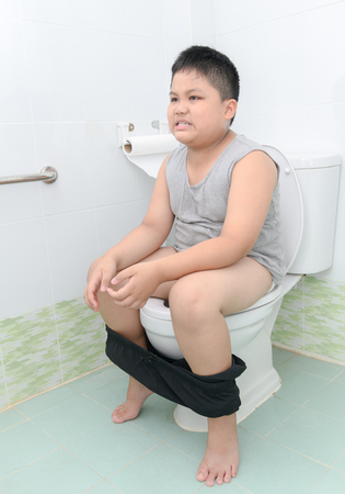 Photo for fat boy suffer stomach and sit in toilet, diarrhea constipation and health concept. - Royalty Free Image