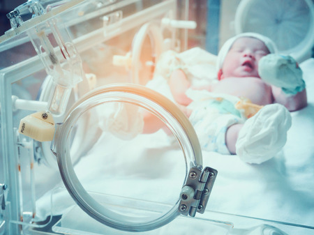 Photo pour Newborn baby girl inside incubator in hospital post delivery room - image libre de droit