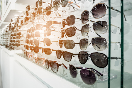 Photo for Sunglasses on display shelves in glasses store - Royalty Free Image