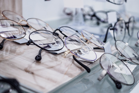 Photo pour Eye glasses on window display shelves in optics store - image libre de droit