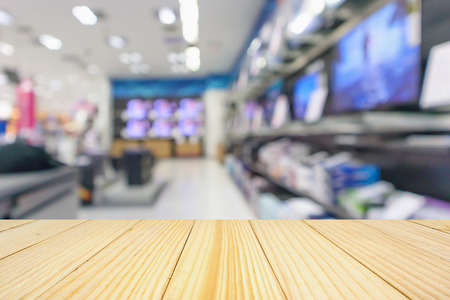 Foto de wood table top with eletronic department store show Television TV and home appliance with bokeh light blurred background - Imagen libre de derechos