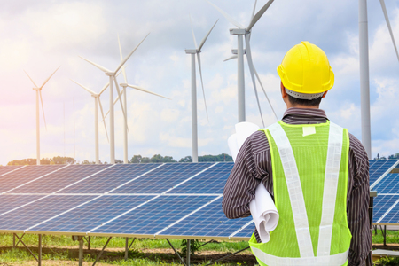 Photo for Young business man engineer with yellow helmet at solar panel and wind generators power plant construction site background - Royalty Free Image