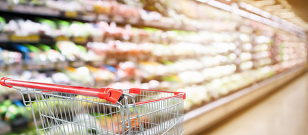 Photo pour supermarket grocery store with fruit and vegetable shelves interior defocused background with empty red shopping cart - image libre de droit