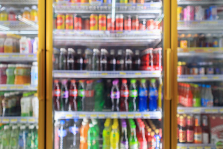 Photo pour supermarket convenience store refrigerators with soft drink bottles on shelves abstract blur background - image libre de droit