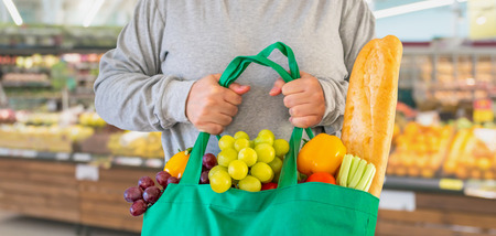 Photo pour Customer hold reusable green shopping bag with fruit and vegetable over Supermarket aisle blur defocused product shelves interior bokeh light background - image libre de droit
