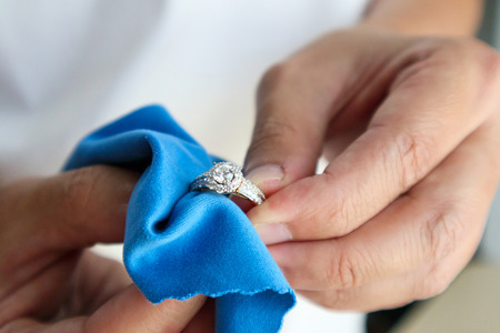 Photo pour Jeweller hand polishing and cleaning jewelry diamond ring with micro fiber fabric - image libre de droit