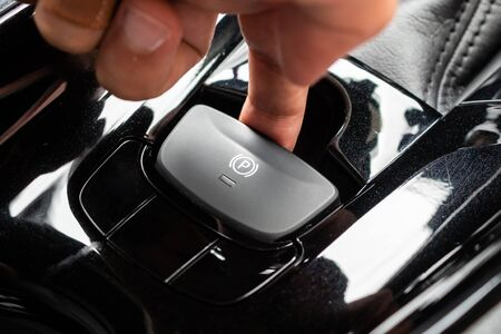 Photo for Hand push on electronic handbrake button in luxury modern car - Royalty Free Image