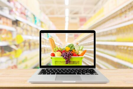Foto de supermarket aisle blurred background with laptop computer and shopping cart on wood table grocery online concept - Imagen libre de derechos