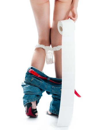 beautiful sexy woman with her back to camera standing with roll of toilet paper. Panties and jeans down. Isolated on white background