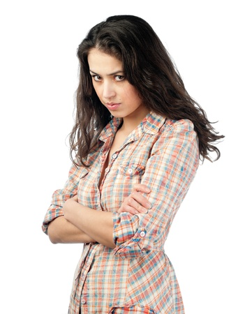 beautiful and unhappy young woman with dark wavy hair looking into the camera with serious expression on her face. Isolated on white background.