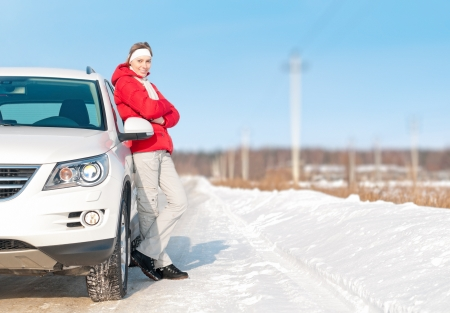 Young girl in red jacket standing near big white car and smiling. Happy road trip with beautiful woman. Active outdoor and winter travel by car. Bright day with clear sky and snow around.