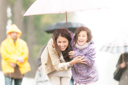 Happy mother and daughter walking in park  Smiling parent and kid hiding under umbrella  Laughing woman and child outdoors  People with umbrellas and person in yellow raincoat in background