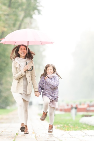 Happy mother and daughter walking in park  Pretty woman holding umbrella  People laugh and enjoy rainy weather  Smiling parent and kid  Sky and green trees in background  Outdoor family activity