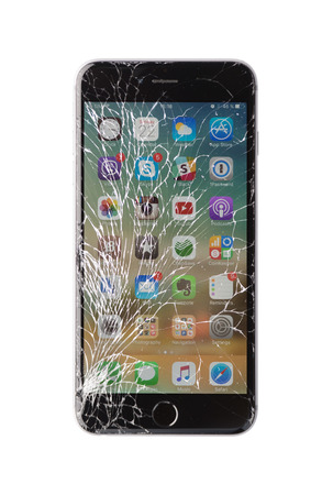 Foto de Moscow, Russia - November 22, 2015: Photo of iPhone 6 plus with broken display. Modern smartphone with damaged glass screen isolated on white background. Device needs repair. - Imagen libre de derechos