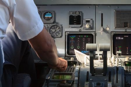 Photo pour Apilot checking instruments in a plane cockpit - image libre de droit