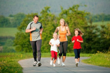 Family doing sport by jogging outdoors with the kids in a beautiful summer landscape in the late afternoon sun