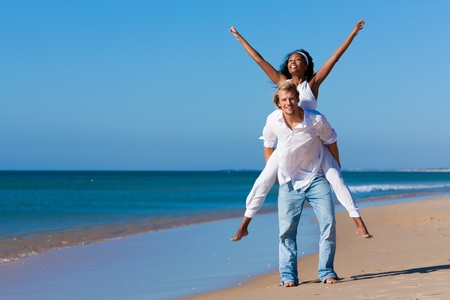 Photo for Happy couple - black woman and Caucasian man - at the beach in their vacation   - Royalty Free Image