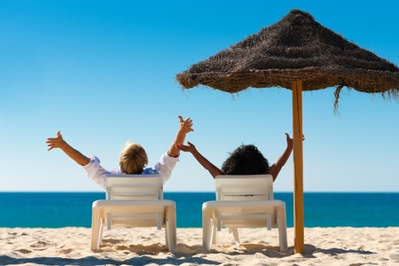 Foto de Couple sitting in sun chairs under an parasol sunshade on a beach stretching arms, feeling free - Imagen libre de derechos
