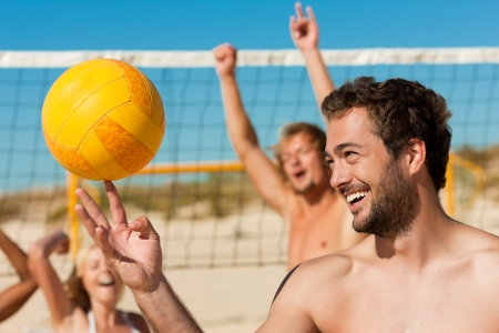 Group of friends - women and men - playing beach volleyball, one in front doing tricks to the ball
