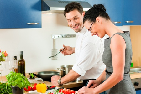 Young couple - man and woman - cooking in their kitchen at home preparing vegetables for salad and pasta sauce