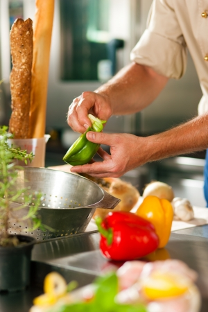 Close up of chef in a commercial restaurant kitchen working; he is preparing vegetables